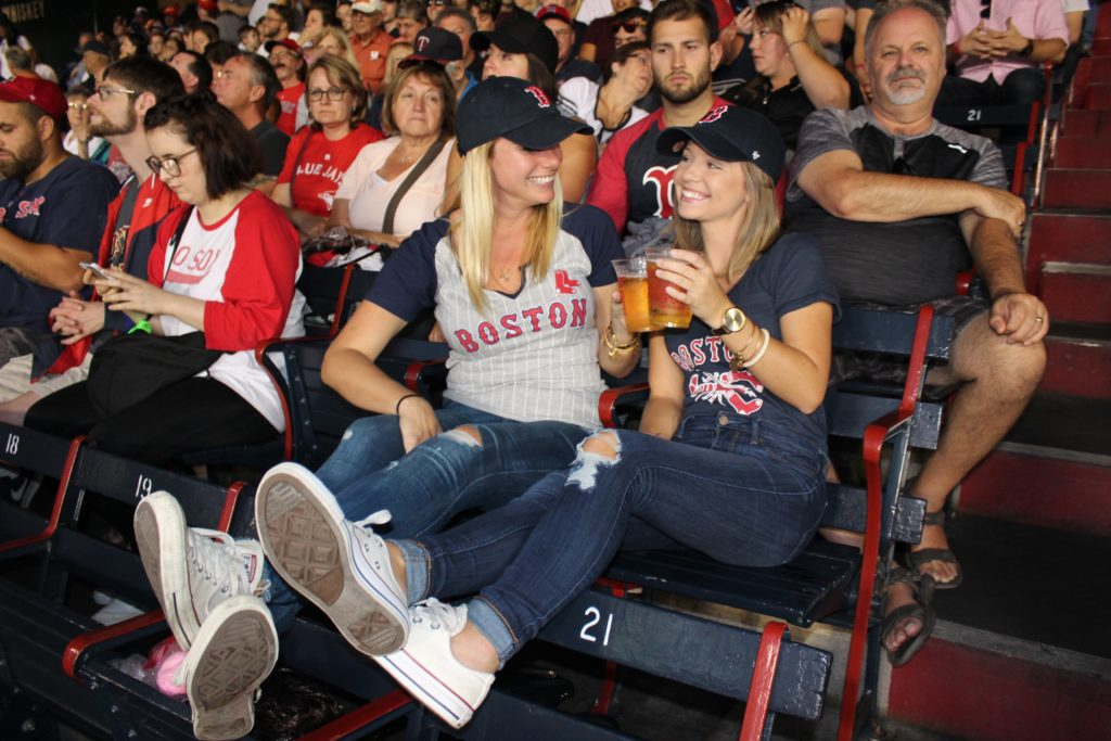 Two girls drinking beer in Fenway park at a Red Sox game