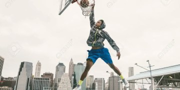basketball player performing slum dunk on a street court. background with manhattan buildings