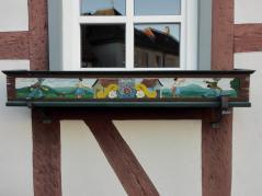 Kunstvoll verzierte Blumenkästen rund um Kirche und Rathaus