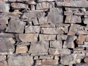 Typisches Muster einer Trockensteinmauer aus Schieferblöcken