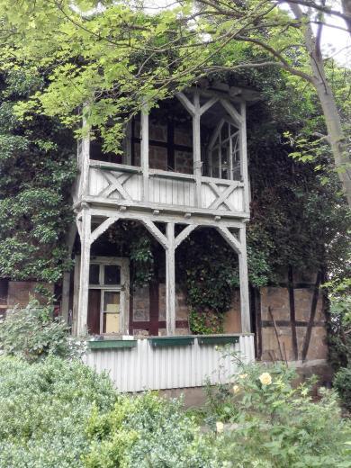 Holzbalkon eins alten, verwunschenen wirkenden Gästehauses neben am Schlosspark