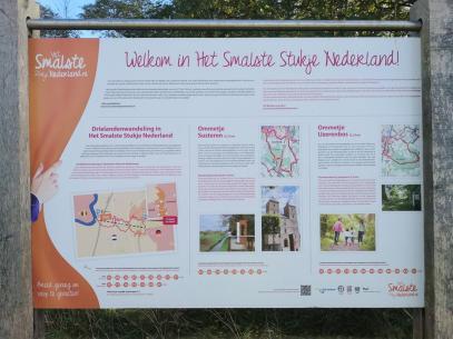 Auf der Tafel steht: Willkommen im schmalsten Stück der Niederlande