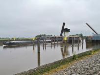 Ein Schiff verlässt das Sperrwerk an der Mündung der Hunte in die Weser