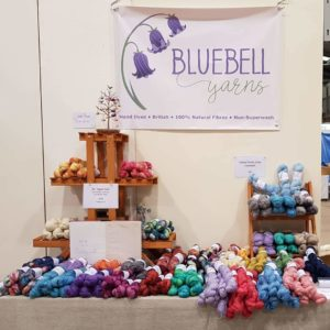 Wonderwool Stall - Colourful yarn on a table with a 'Bluebell Yarns' banner behind.
