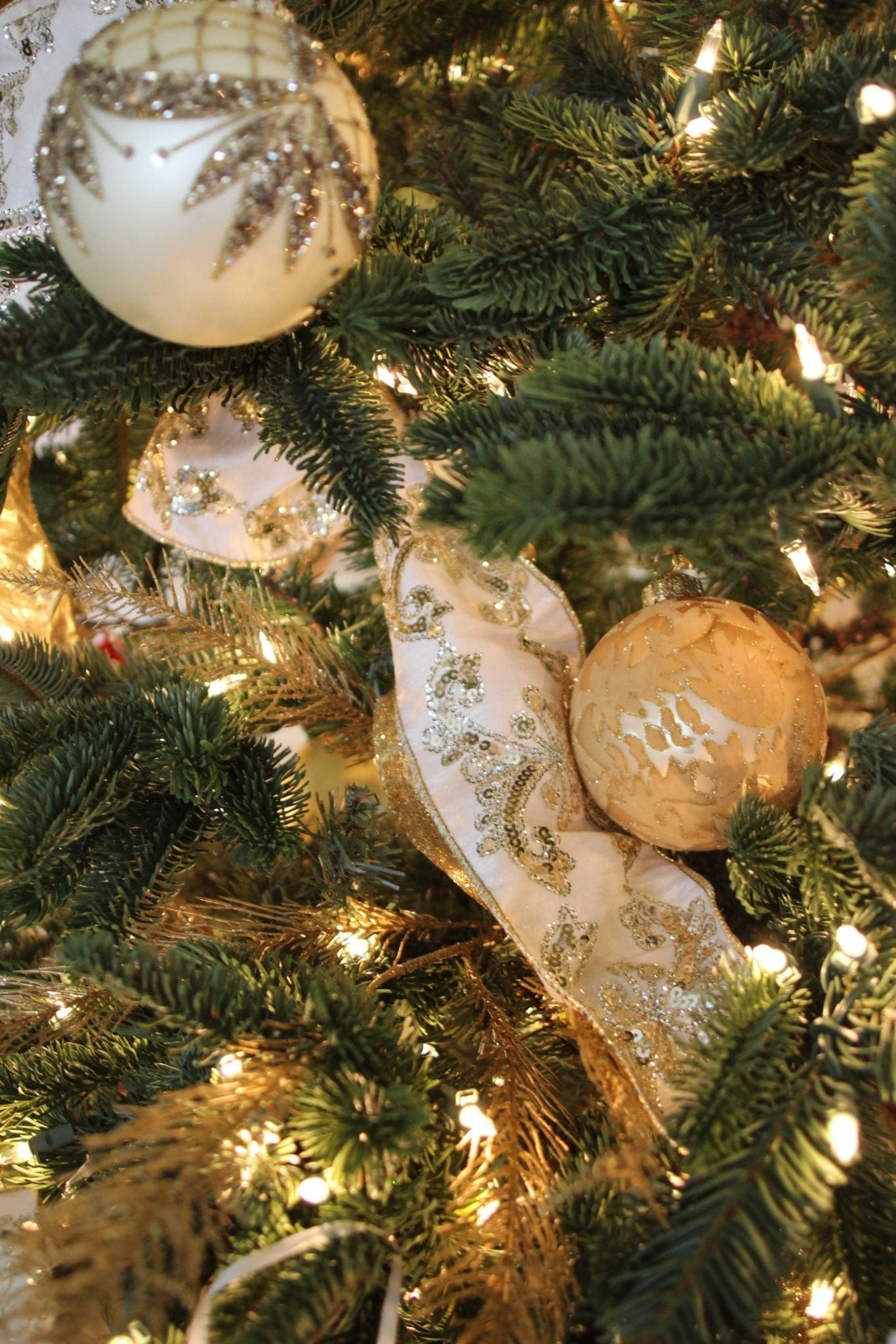 Christmas ribbon used in a Christmas tree with white and gold ornaments.