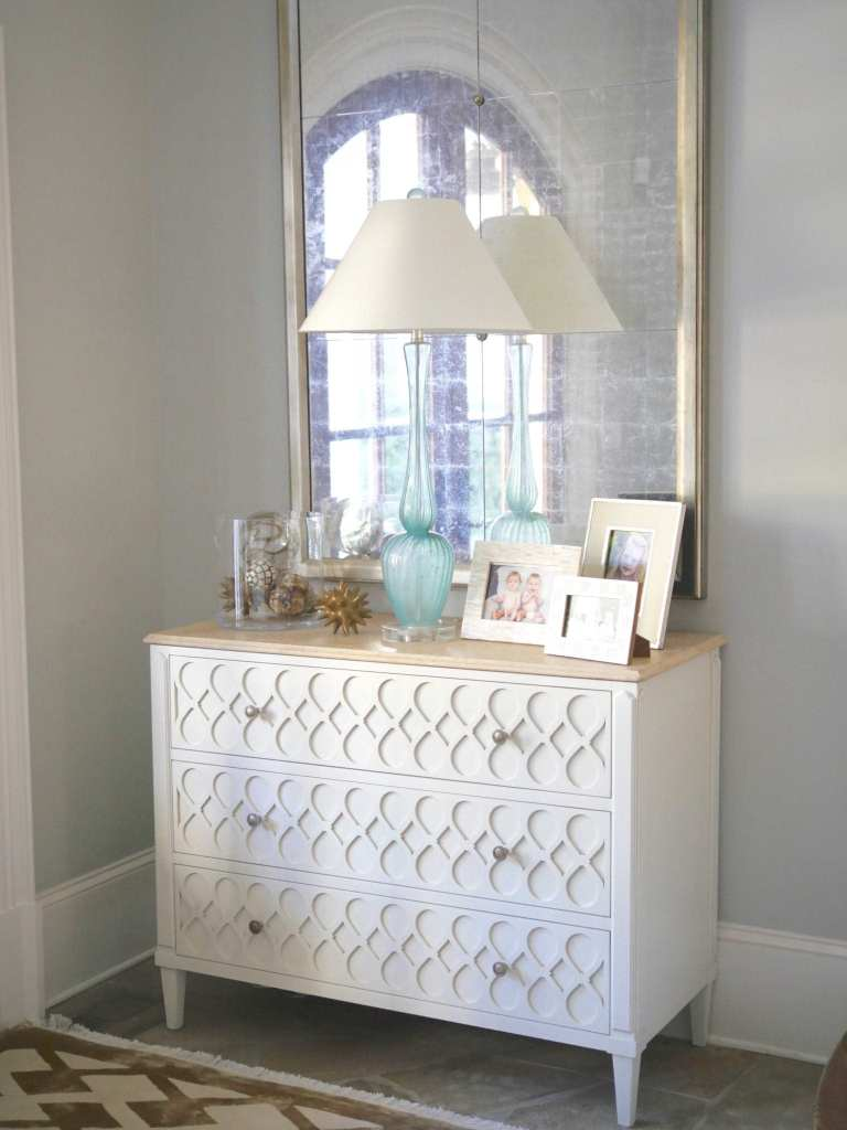 Foyer entry table with turquoise lamp. Light wood console with gold distressed mirror and light colored accents. Brushed Aluminum paint color.