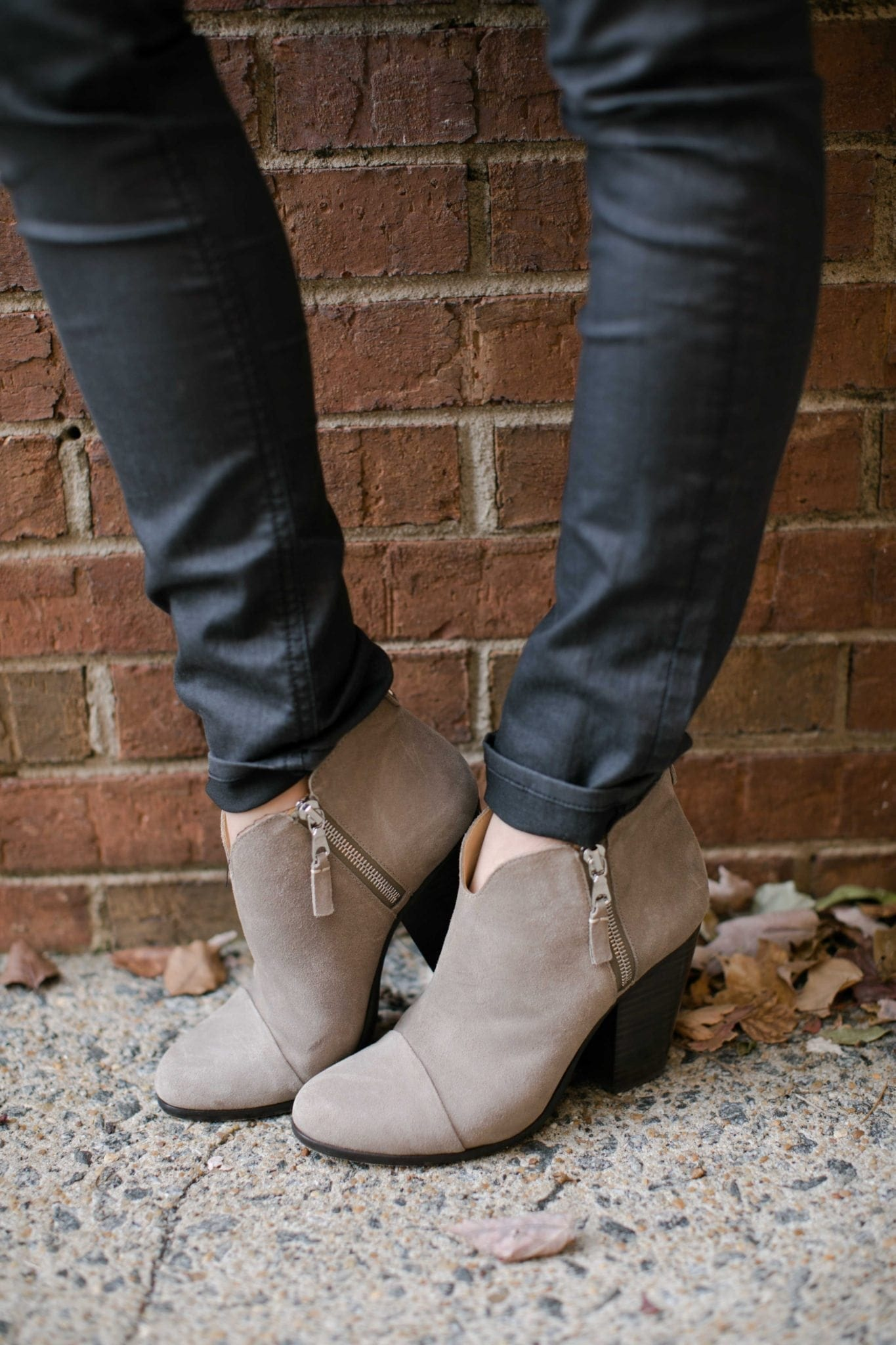 neutral booties with zippers on the side standing by fall leaves on the street with black jeans