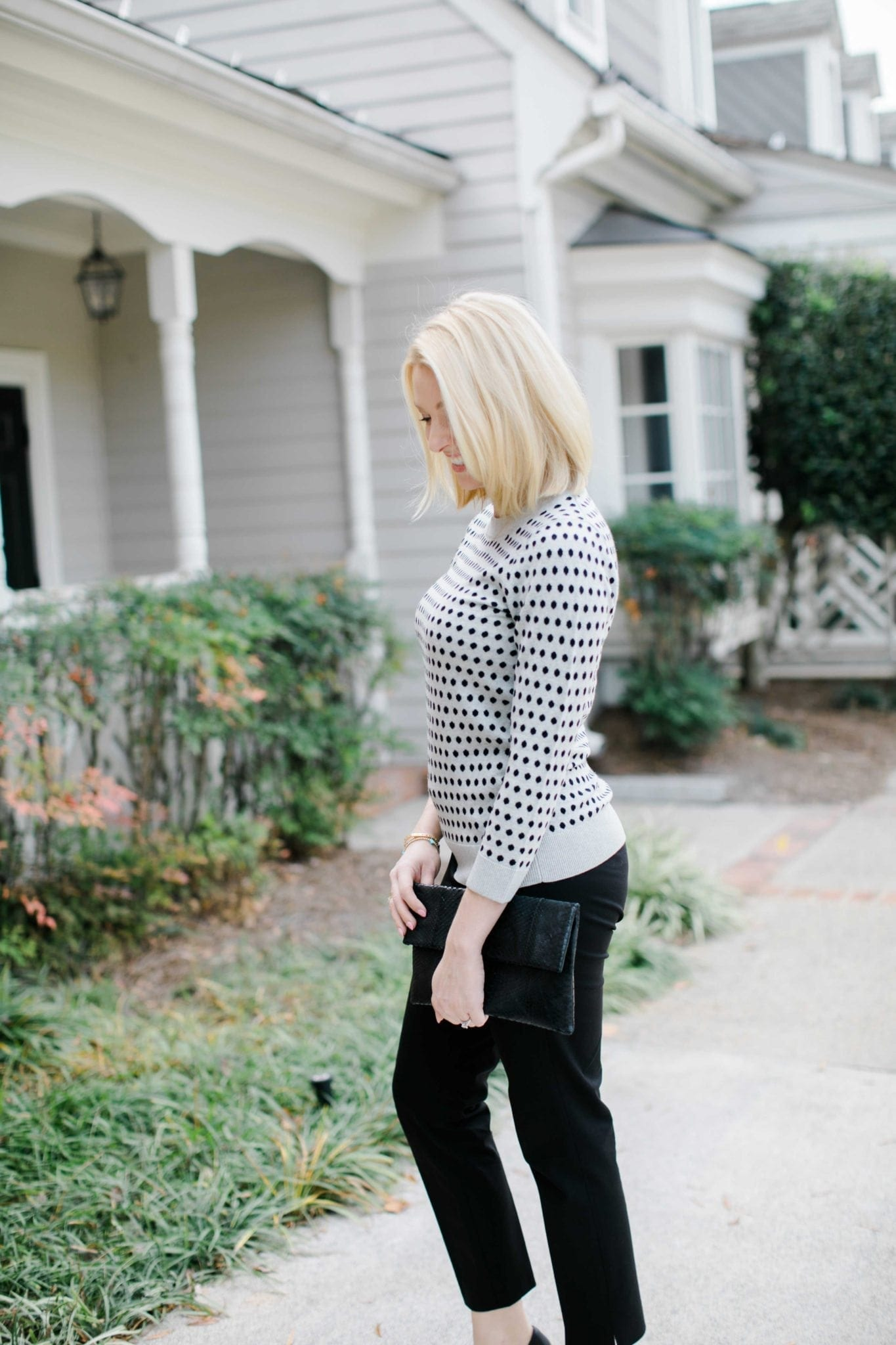 blonde girl wearing polka dot sweater and carrying a black snakeskin clutch purse