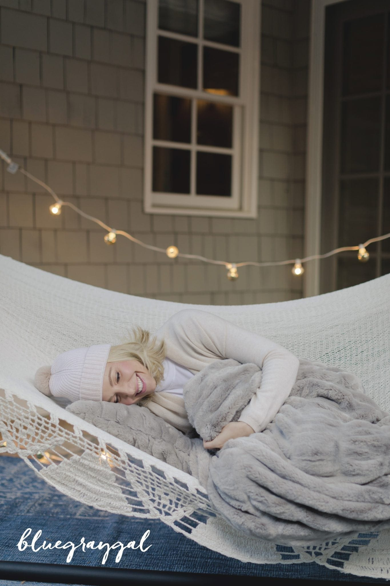 faux fur throw blanket from pottery barn with kelly page laying in woven hammock and lights hanging outside house