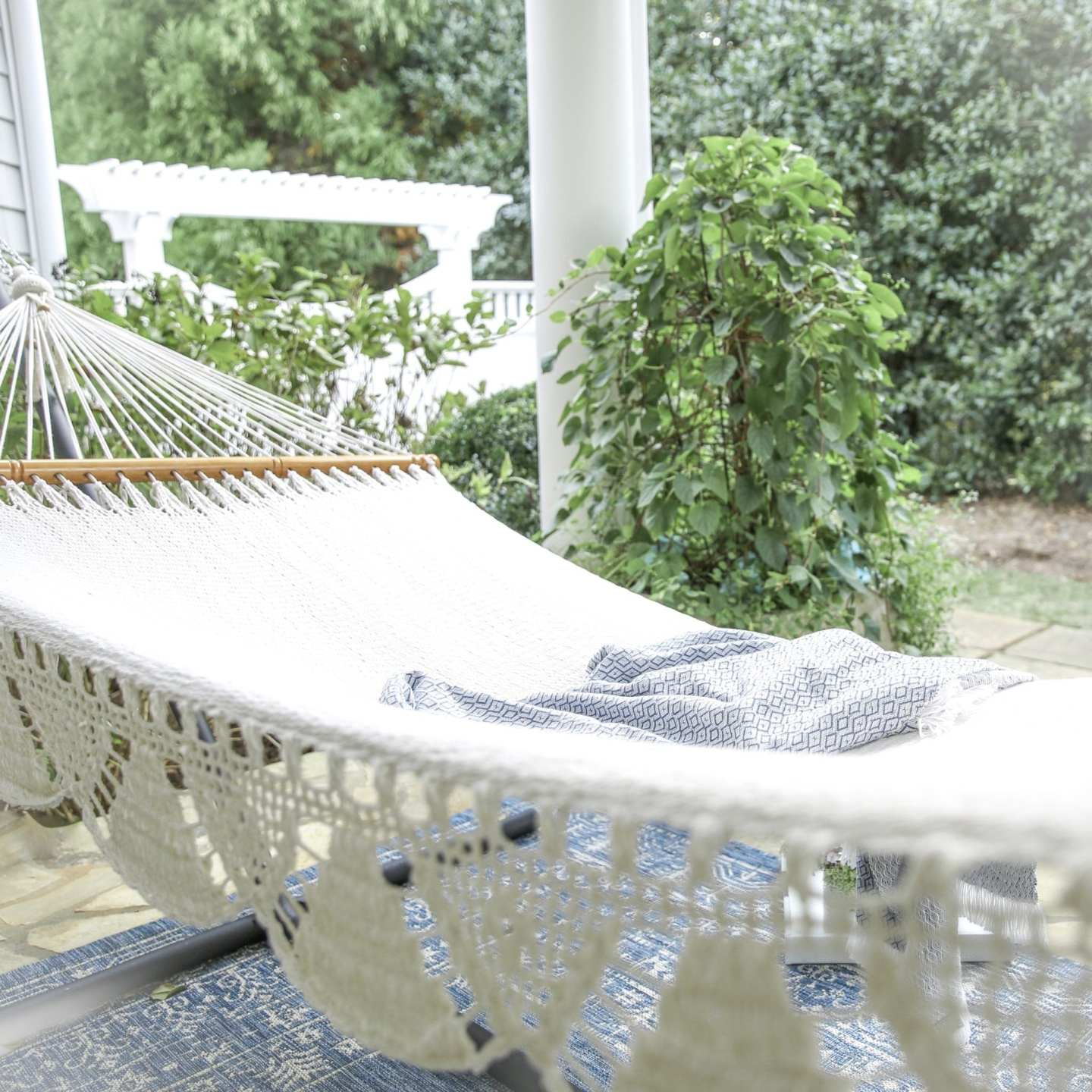 woven hammock outside with indoor outdoor blanket by cape code white gate and climbing hydrangea bush