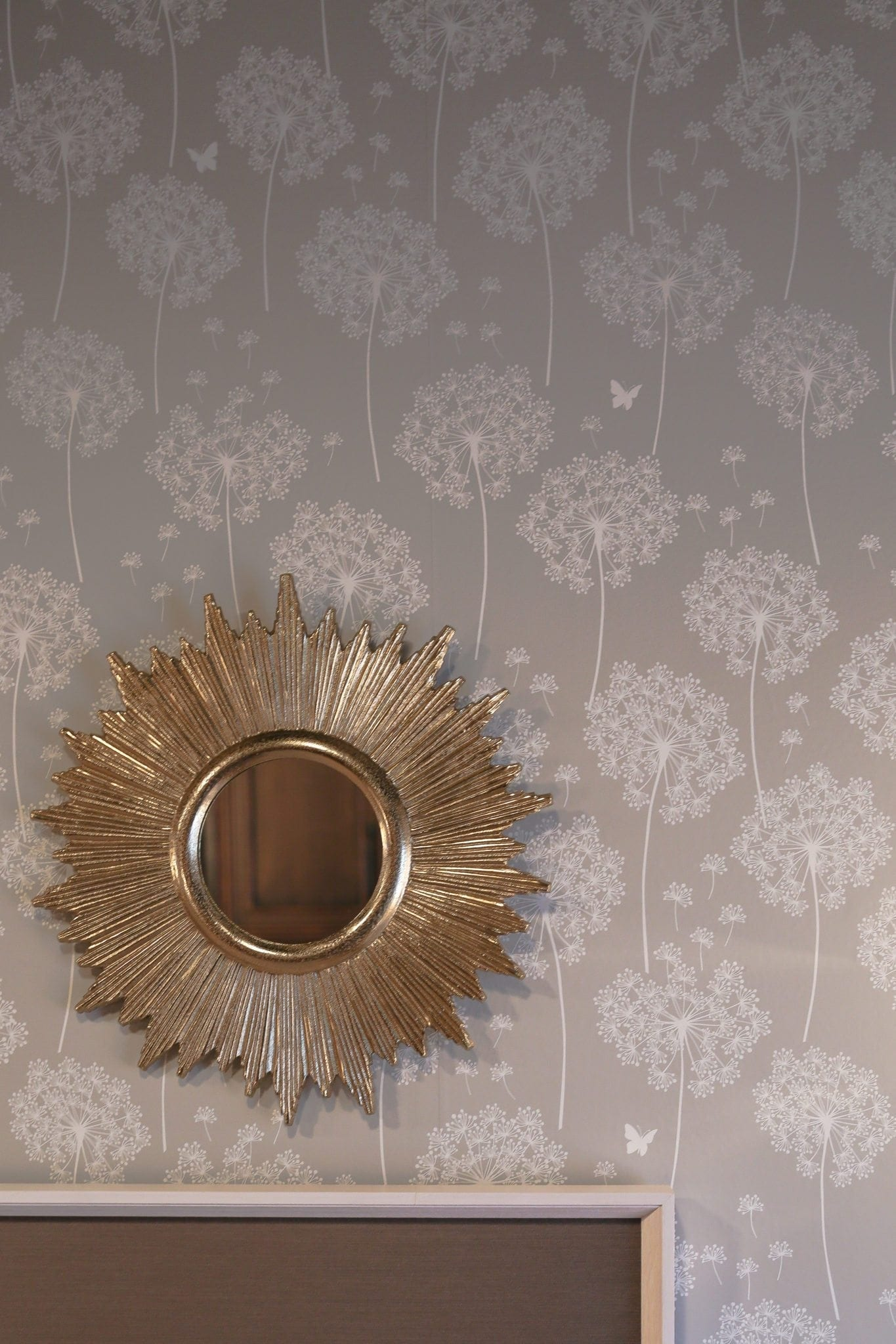 Starburst gold mirror with gray reusable wallpaper.