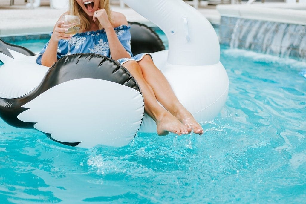 Atlanta Lifestyle Blogger Kelly Page in giant pool floats for adults.