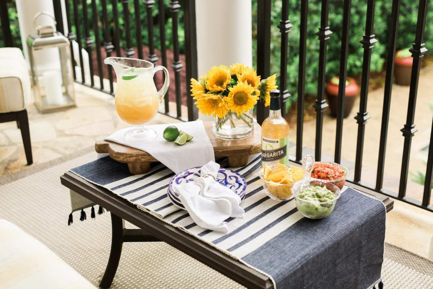How to decorate for outdoor party. Yellow sunglasses and margarita pitcher on wooden pedestal. Blue and white table runner.
