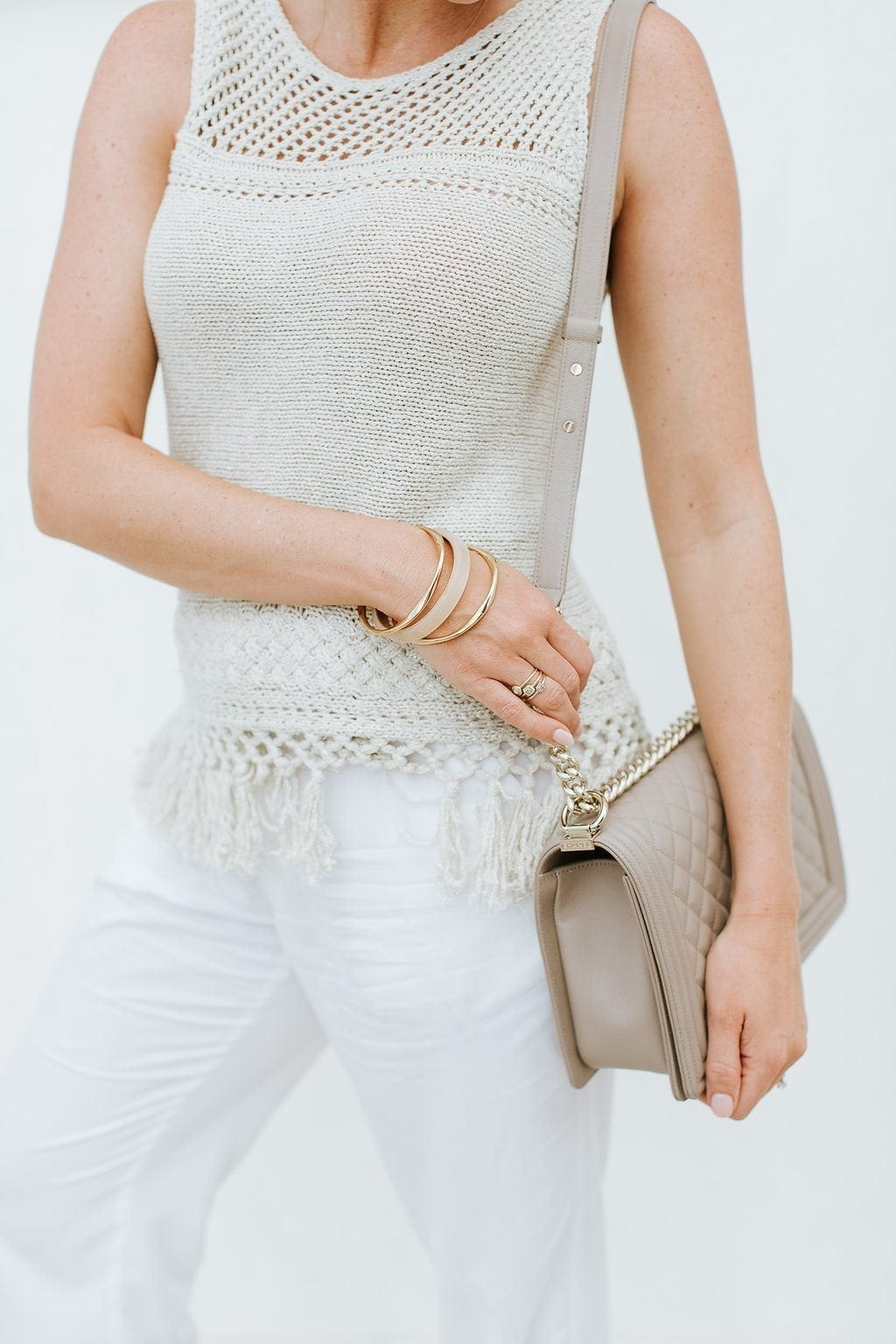 A not so basic sweater! Gold fringe sweater with neutral Chanel Boy bag and gold and nude bangle bracelets. White and gold summer outfit for family photos.