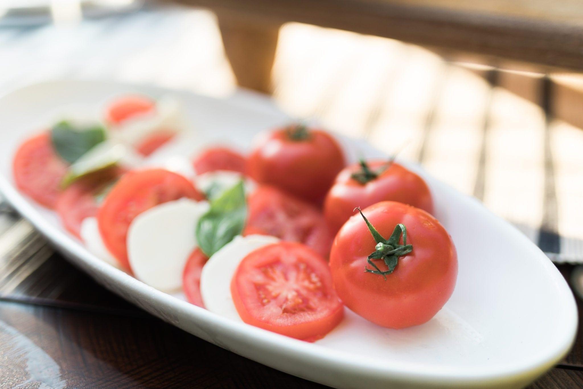 Caprese salad on white platter.