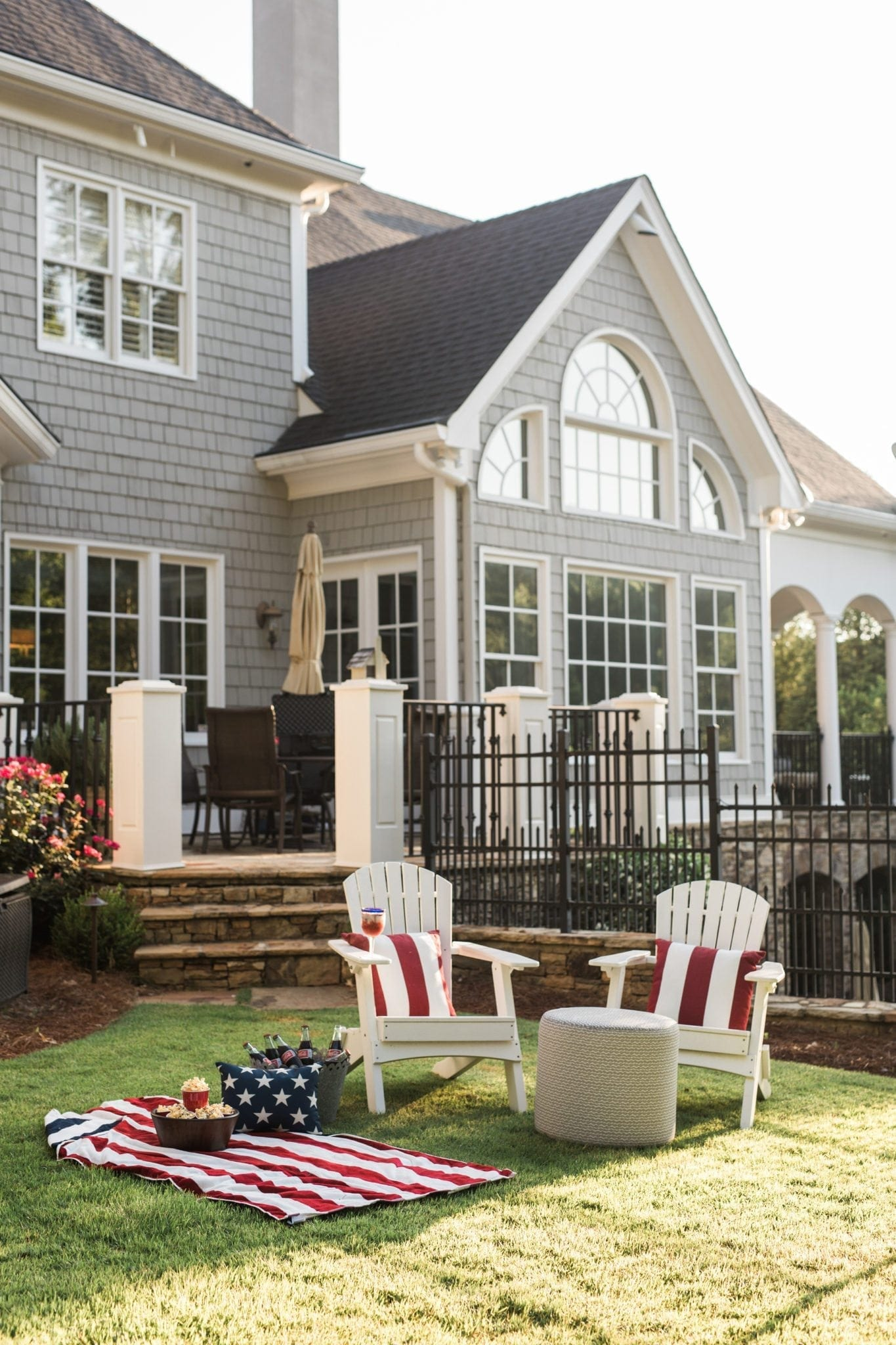 White wood adirondack chairs with red and white strip outdoor pillows set the stage for a Fourth of July backyard party. Gray shingle house Cape Cod style house with Americana felt an outdoor porch setting.