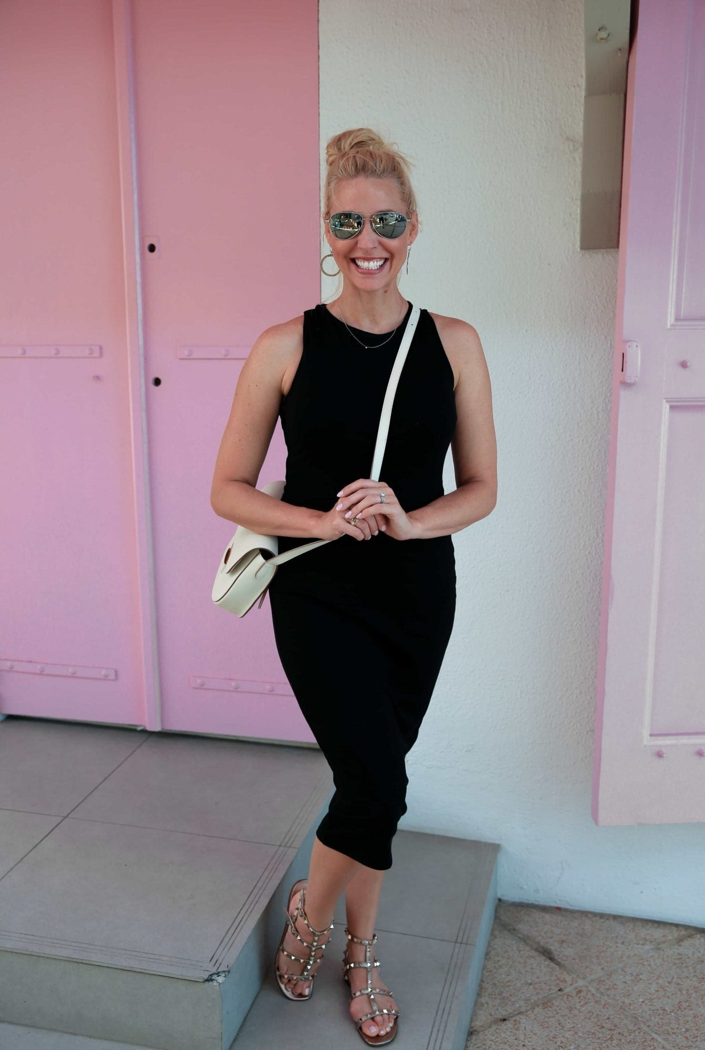 Black fitted dress from White House Black Market with white cross body bag and Valentino Gold Studded Sandals. Photo in front of pink door in St Barths.