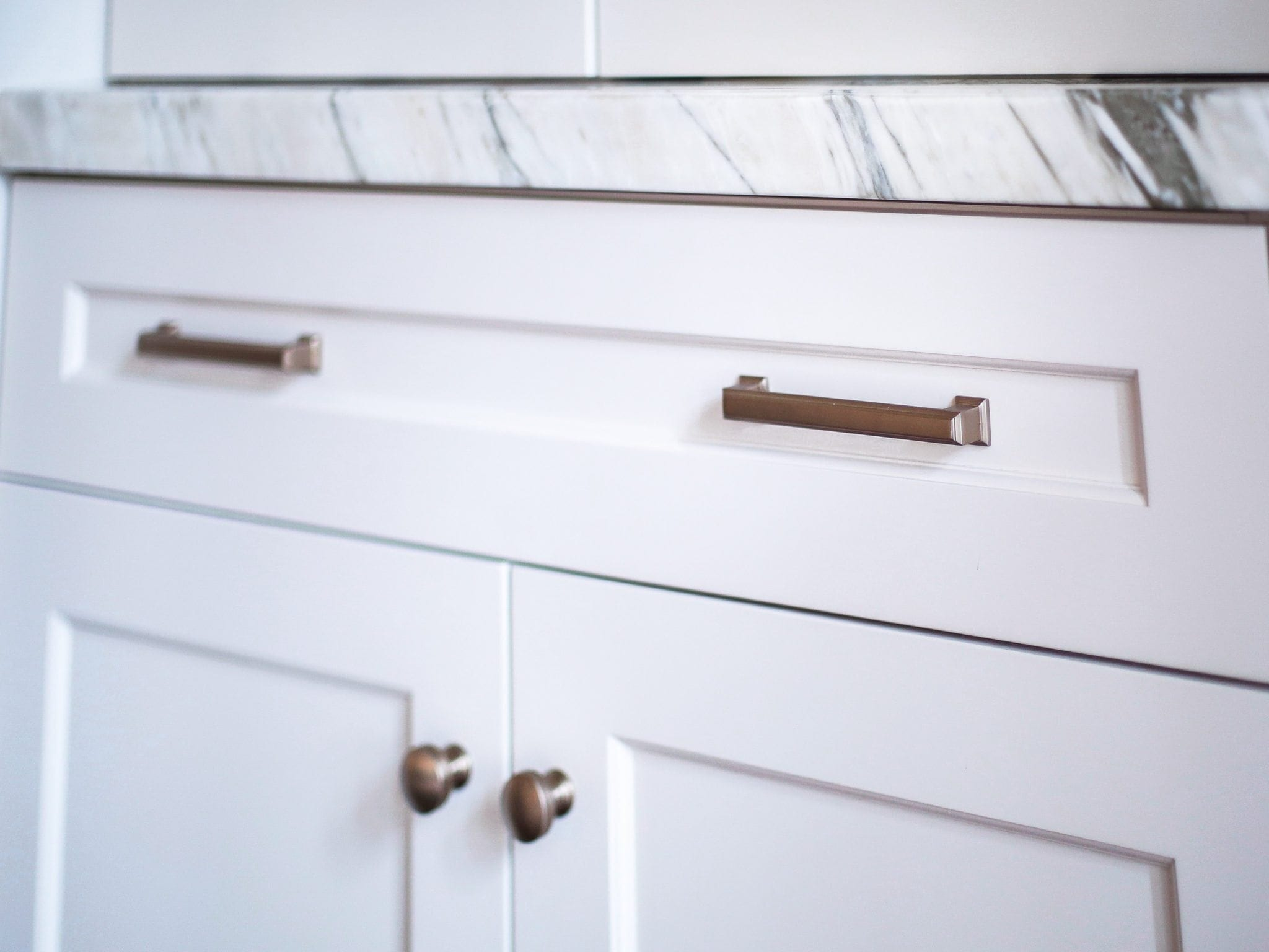 Gold hardware on white cabinets.