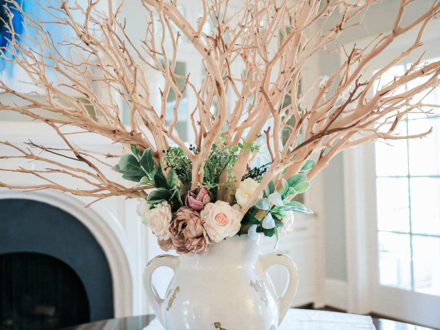 fake flowers that look real in vase using manzanita stick branches and roses.