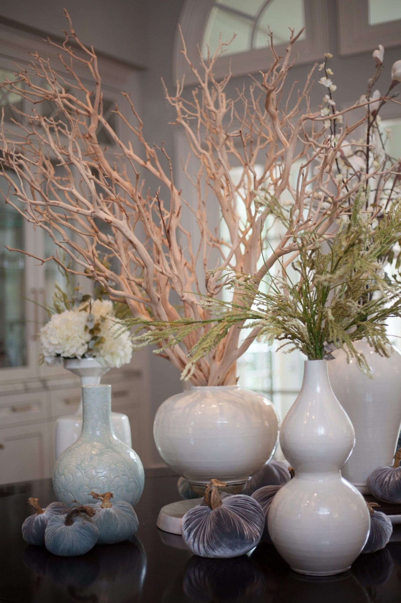 Silk floral arrangements in white urns. Beautiful clean white centerpiece with manzanita branches for a round dining room table.