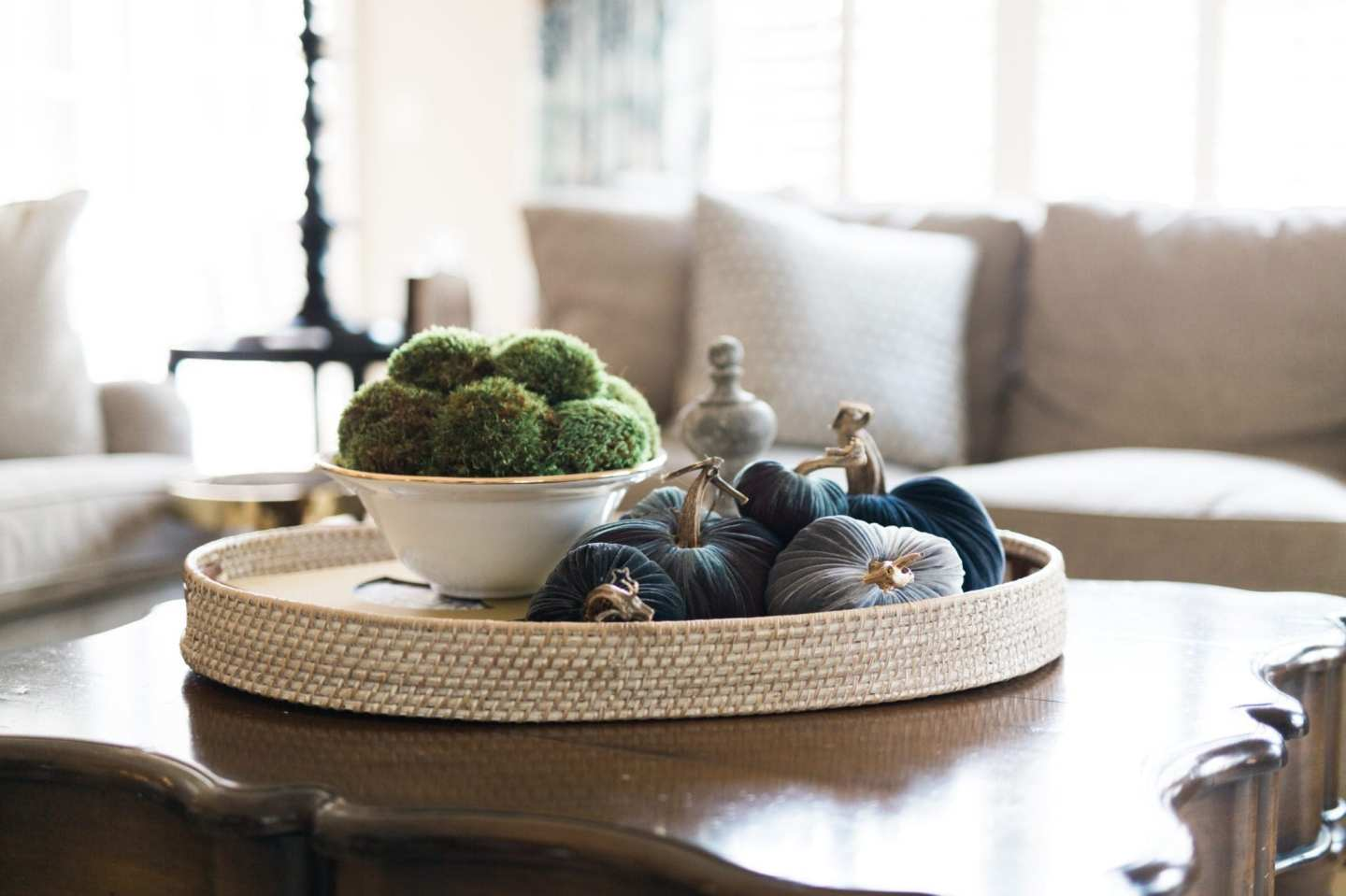 Plush Pumpkin on a rattan tray on a family room coffee table.