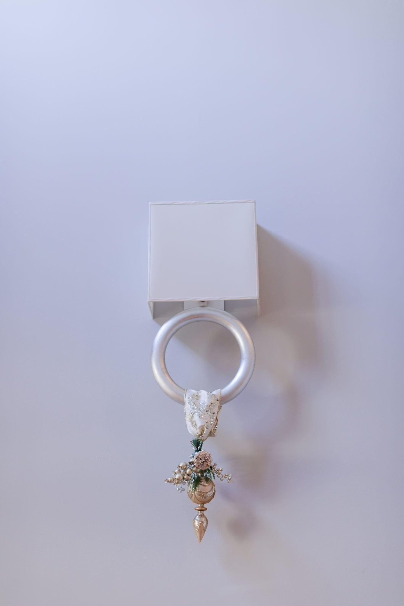 Ornament hanging from light fixture. Silver sconce with shade.