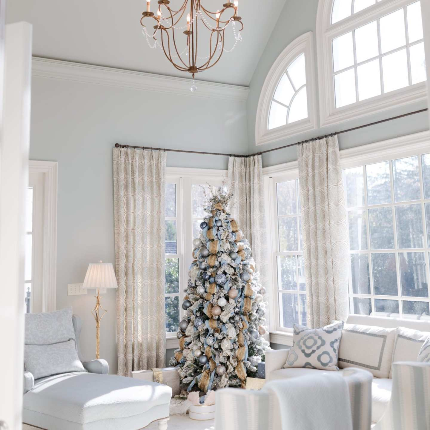 Blue Christmas decor. Blue paint in light blue living room with chandelier and blue chez lounge.