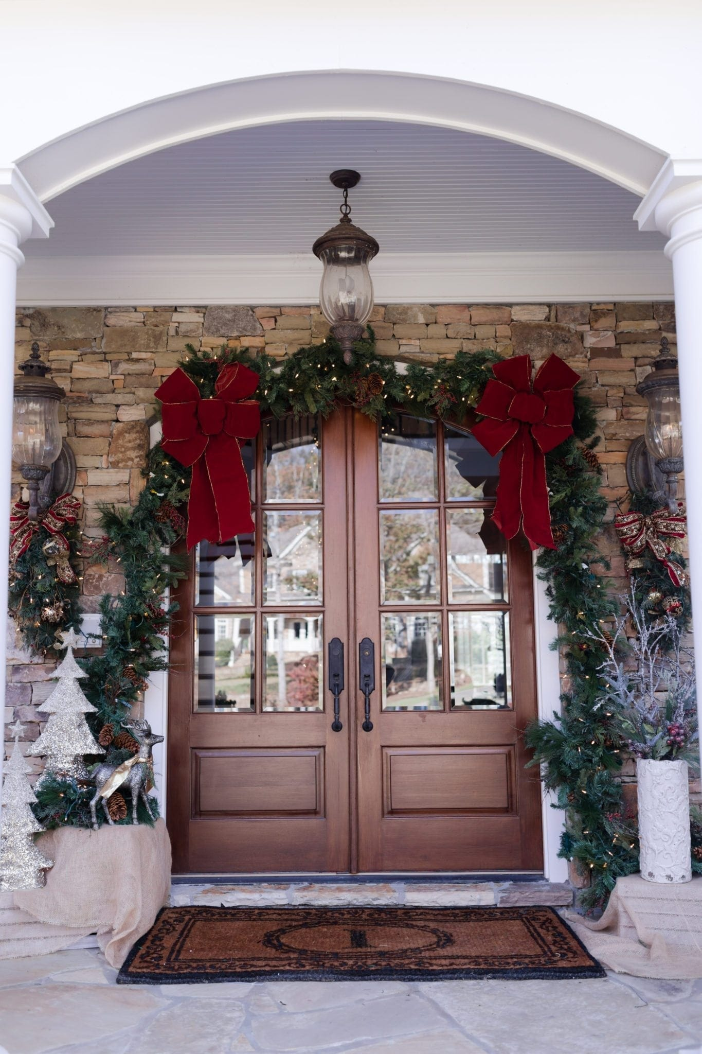 Garland hung around door frame with big oversized red ribbons and gas lanterns. Front door decorating ideas for Christmas.