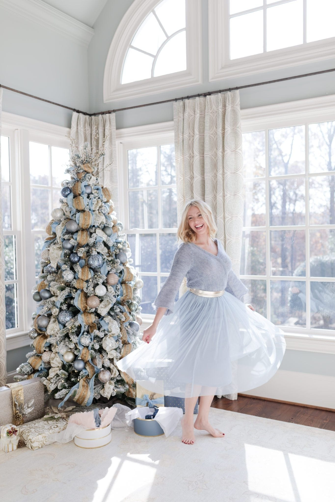 Light blue dress from Anthropologie. Anthropology dress with White House Black Market Obi belt. bluegraygal Kelly Page lifestyle blogger twirling by her blue Christmas tree.