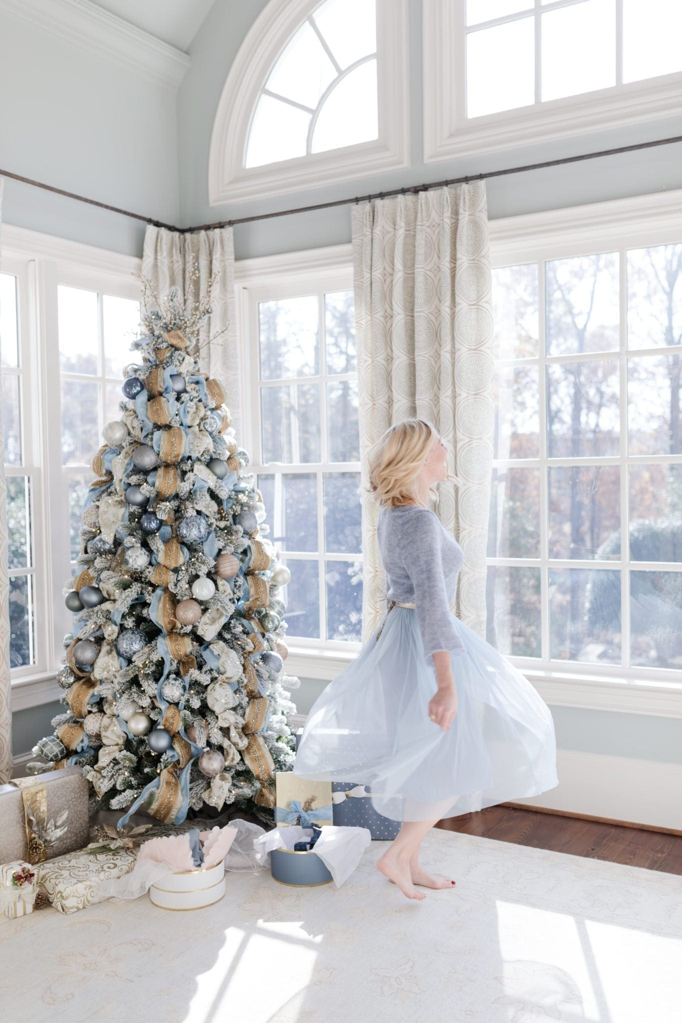 blue Christmas tree decor and light blue sweater and tulle dress.