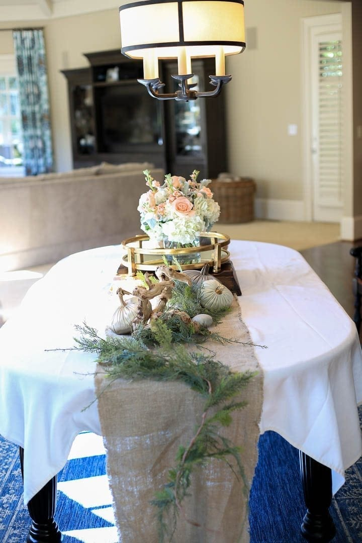 Burlap runner with greenery down the center with gold round tray and pumpkins for fall decor in a kitchen.
