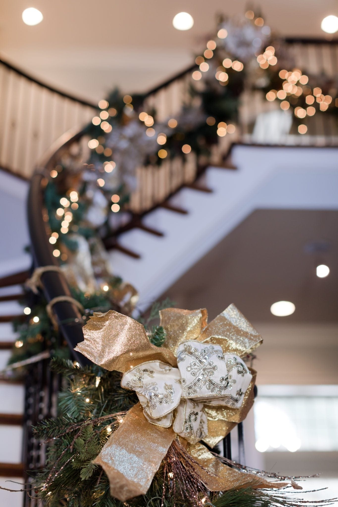 Gold and ivory box on artificial garland swagger on foyer staircase.