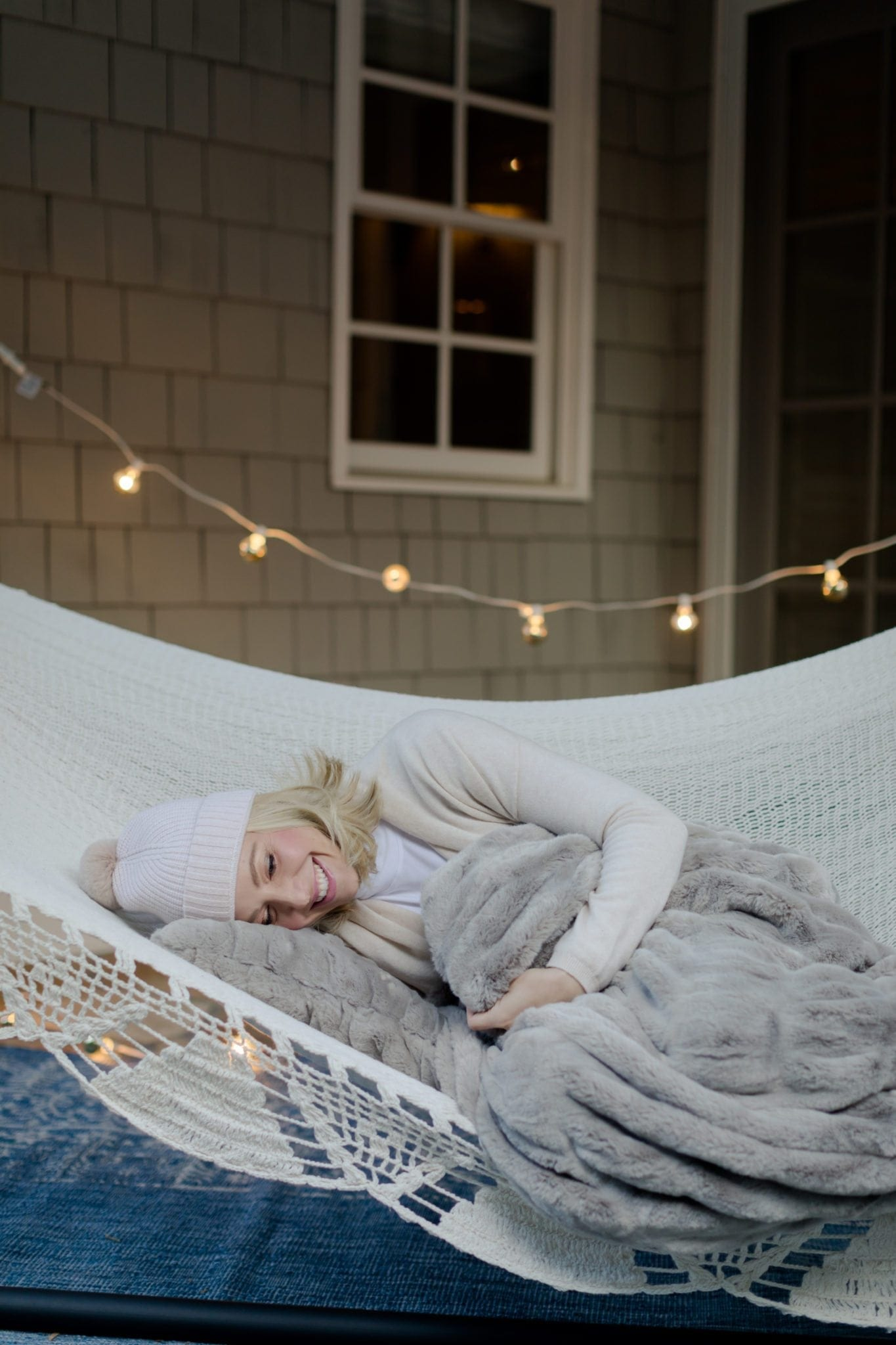 Fall home decor for outdoors. Outdoor hammock with soft pink beanie hat and cozy blanket.
