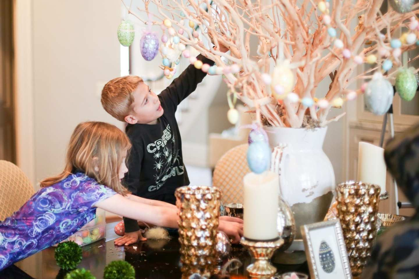 Kids decorating for Easter with Easter egg garland and Egg ornaments handing from branch centerpiece.