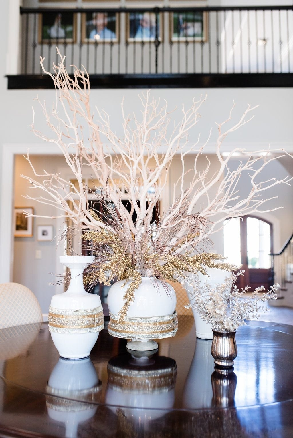 Manzanita Branches used as dining room centerpiece for round dining room table. White urns filled with branches and gold ribbon detail wrapped around urns.