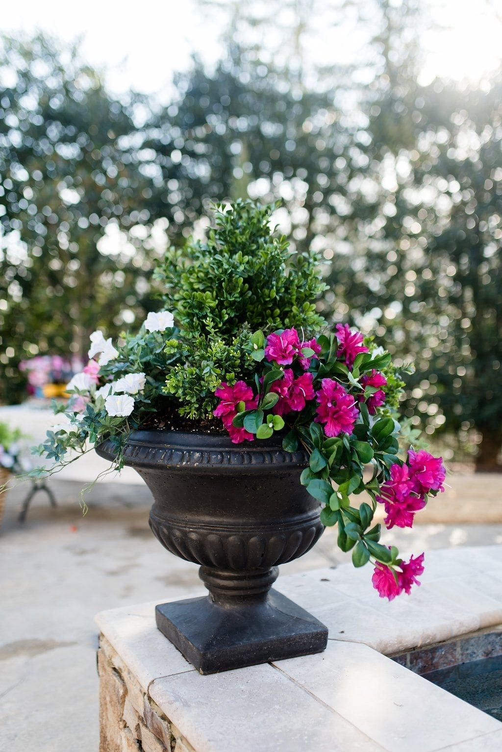 Silk flower arrangements outside. Faux azalea mixed with silk petunias in poolside container. No more need to worry about containers who get to much sun - go faux and no one will know!