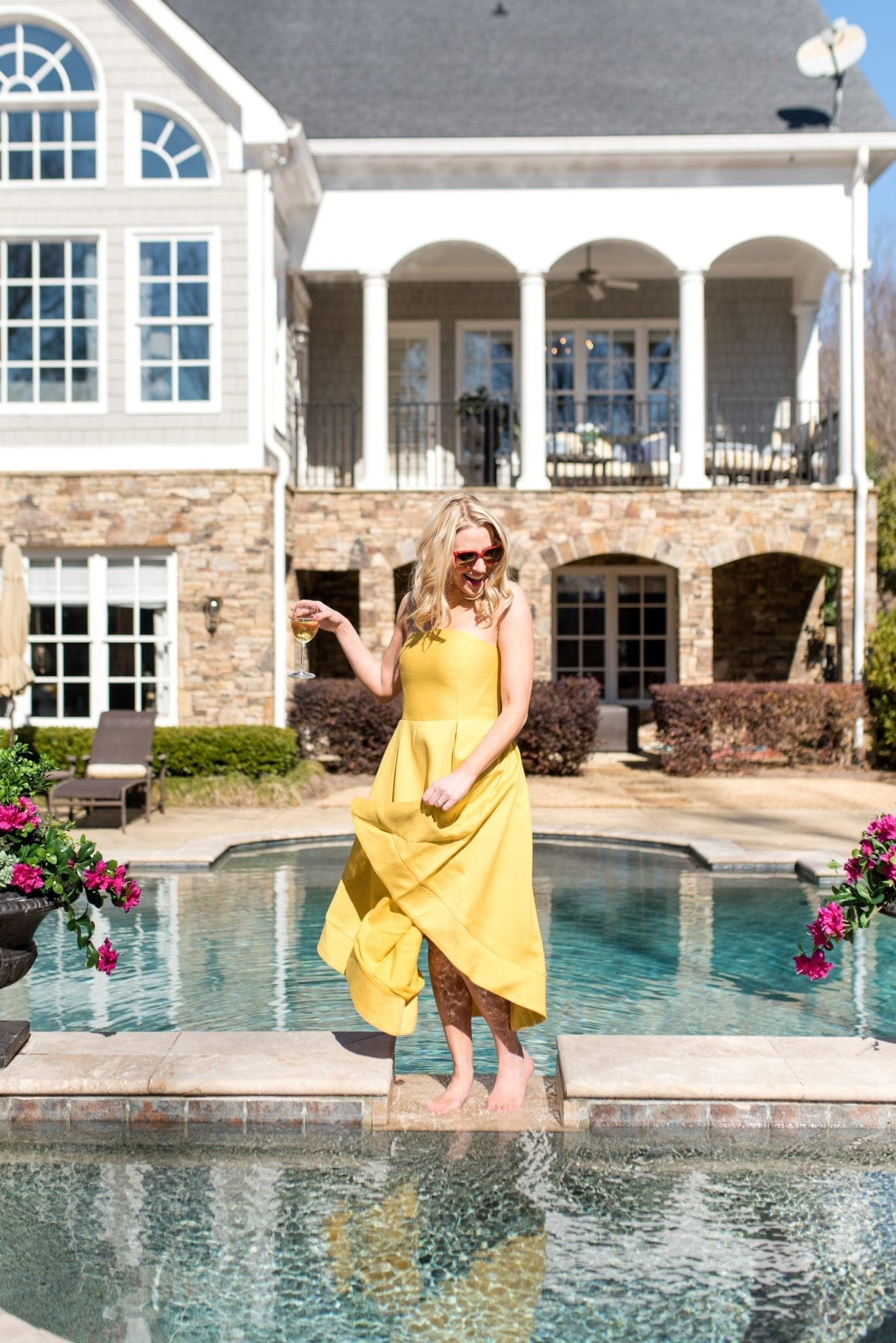Yellow strapless dress. Cape Cod style home exterior and pool.