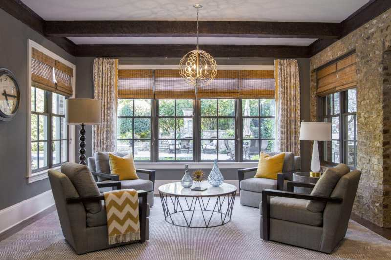 Modern basement decor. Wood beams, stone walls and Currey and Company light fixture. Gray painted walls with pops of yellow color.