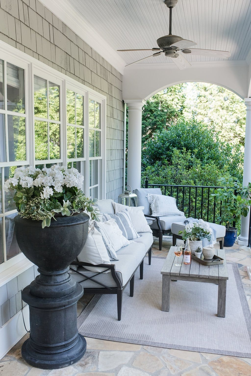 Gray and white outdoor furniture. Teak table and cushioned outdoor furniture.