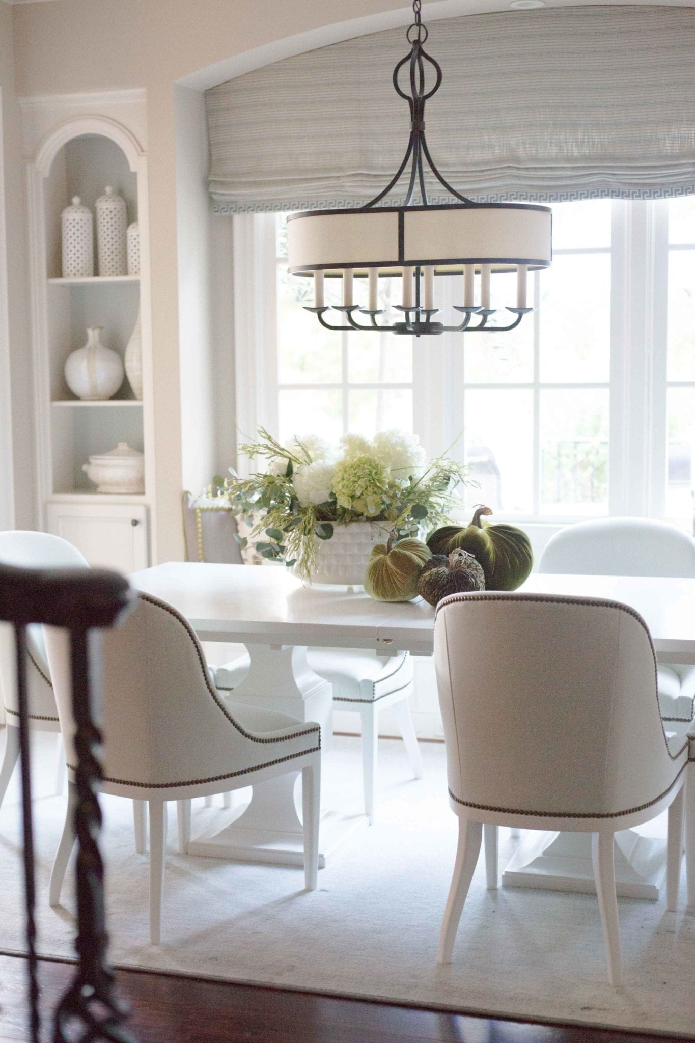 Green velvet pumpkins in white kitchen table. Pretty fall decor. White kitchen table with light blue chairs and white hydrangea arrangement for a soft and pretty fall table!