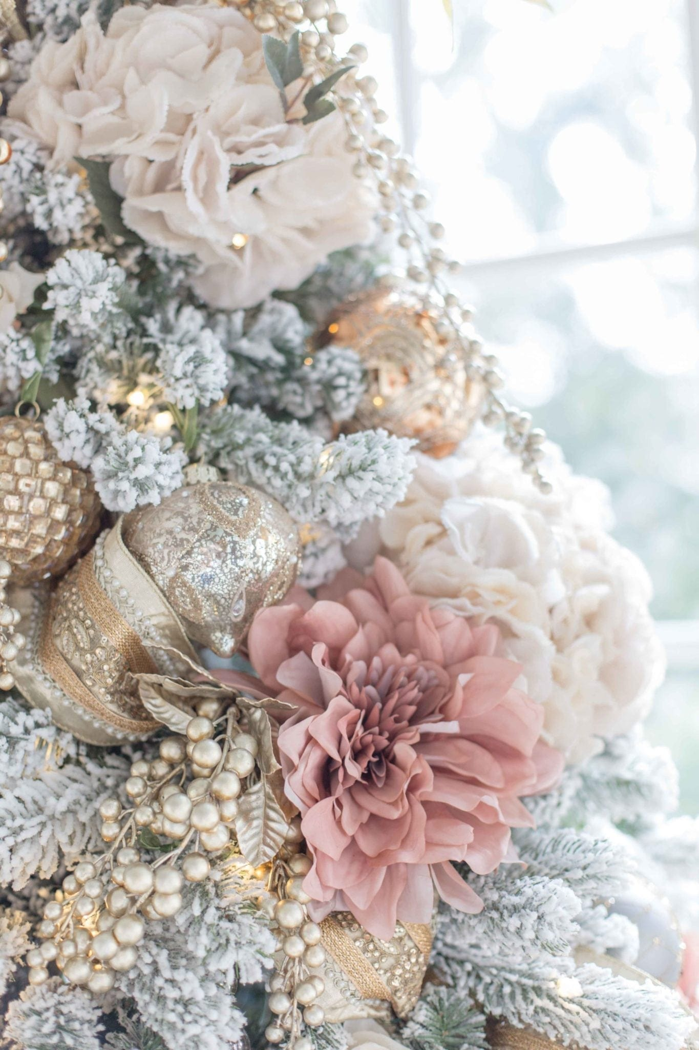 Faux flowers on a Christmas tree. Use fake flowers to add a new element to your holiday tree along with gorgeous ornaments!