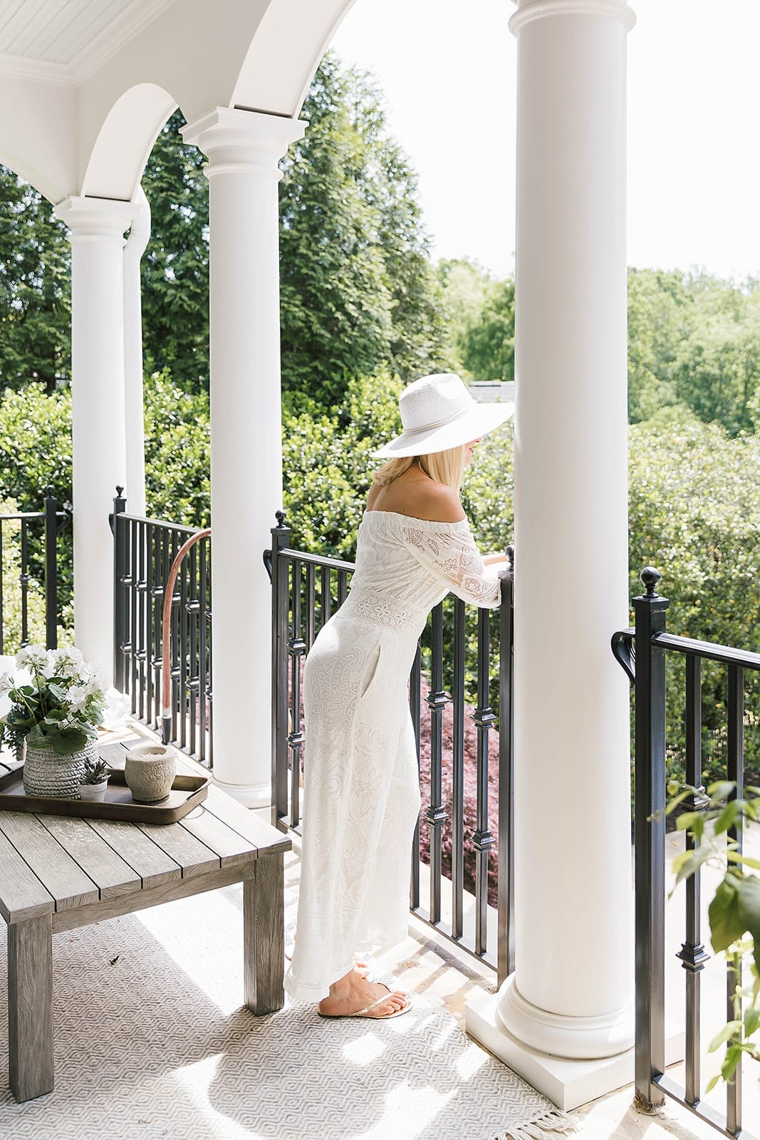 Vacation Outfit for Italy. White lace jumpsuit with white summer hat on lifestyle blogger, Kelly Page, for BlueGrayGal.