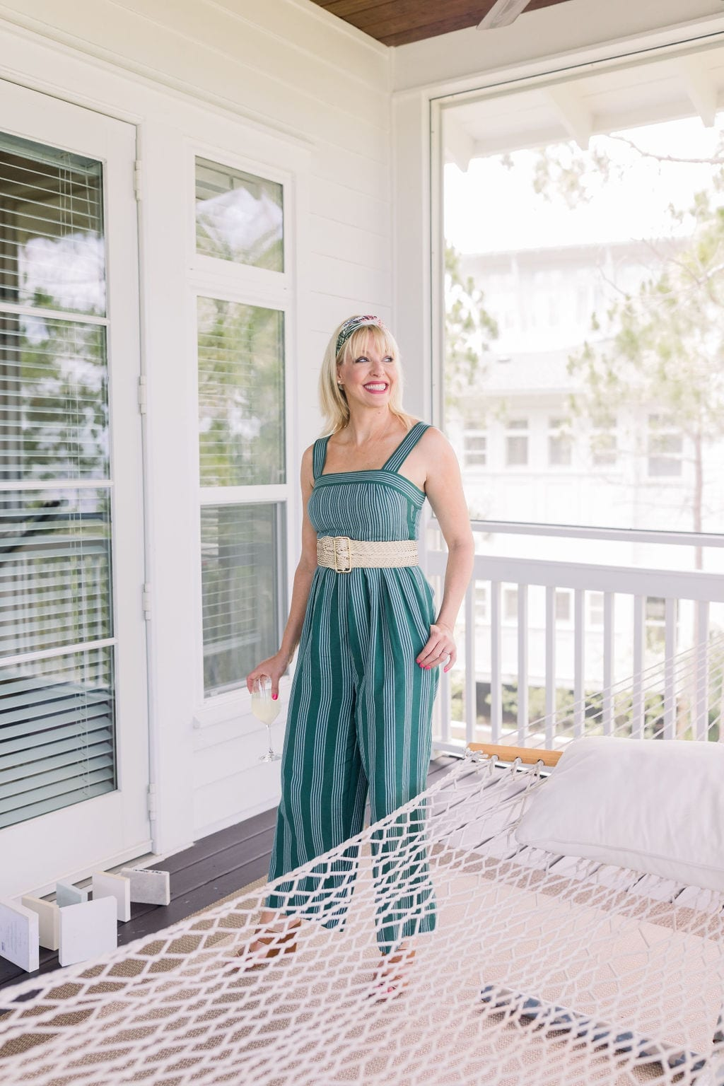 Anthropologie jumpsuit in emerald green with wicker belt and floral headscarf. Great summer jumpsuit for women with short torso's and long legs.