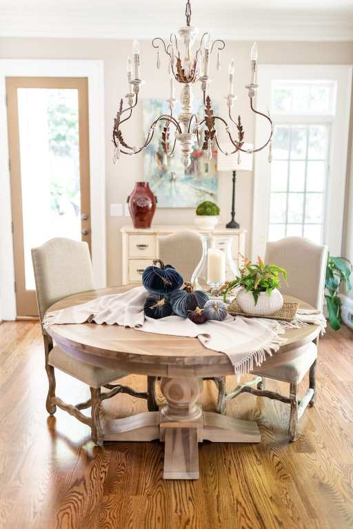 Thanksgiving Table set up with Plush Pumpkin. Rustic kitchen with chandelier and round wood dining room table.