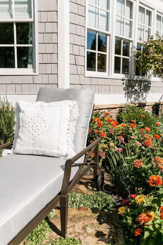Andover Collection chaise lounge. Zinnia flower garden in Atlanta home. Oversized Chaise Lounge Chair in gray with white Serena and Lily outdoor pillow.
