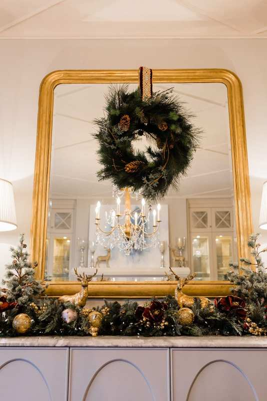 Magnolia garland with lights. Wreath hanging from mirror with ribbon. Dining Room buffet set with candles, reindeer decorations and faux Christmas trees.