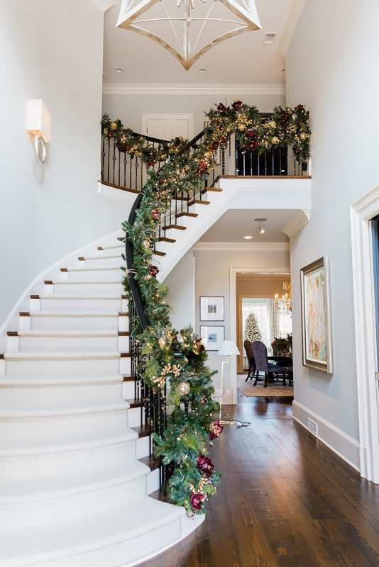 Staircase Garland with red and gold garland. Pre-lit garland from Frontgate with gold banister ties.