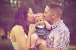 Couple kissing a baby