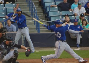 Josh Donaldson swings while Jose Bautista looks on from the on-deck circle