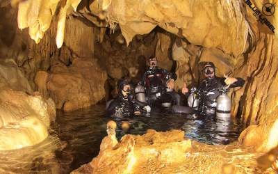 Sidemount Divers Explore a Dry Room at Spider Cave. Their cylinders are staged for decompression as part of a DPV Stage Cave course.